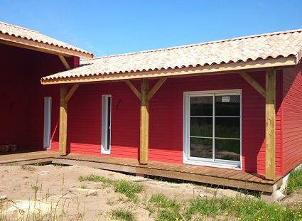 une maison bois bardage rouge en L